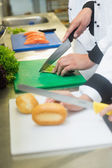 Close up of chefs slicing bread rolls and asparagus — Stock Photo