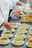 Bowls with soup being garnished — Stock Photo