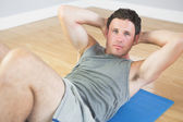Calm sporty man doing sit ups on blue mat — Stock Photo