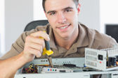Handsome content computer engineer repairing open computer — Stock Photo