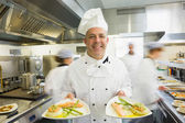 Mature head chef presenting proudly two dinner plates — Stock Photo