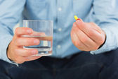 Close up of man holding a pill and glass of water — Stock Photo