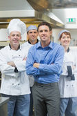 Handsome manager posing with some chefs — Stock Photo