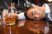 Drunk and unconscious businessman lying on a counter — Stock Photo
