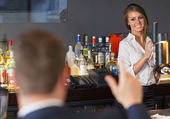 Handsome man ordering a drink from gorgeous waitress — Stock Photo