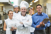 Head chef posing with the team behind him — Stock Photo