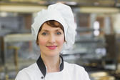 Happy female chef posing in a kitchen — Foto Stock