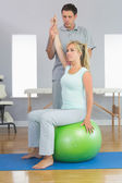 Physiotherapist correcting patient sitting on exercise ball — Stock Photo