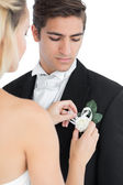 Young bride pinning a flower on her husbands suit — Stock Photo