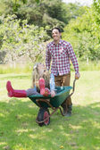 Man pushing his girlfriend in a wheelbarrow — Stock Photo