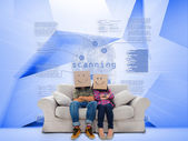 Couple with cartons on head sitting on couch under holographic finger print — Stock Photo
