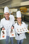 Two young chefs presenting dessert plates — Foto Stock