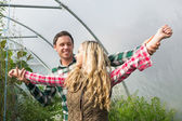 Sweet couple posing in their greenhouse — Stock Photo