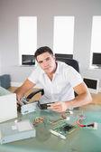 Atraktivní počítačový inženýr sedící u stolu drží hardwaru — Stock fotografie