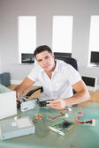 Attractive computer engineer sitting at desk holding hardware — Stock Photo