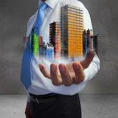 Close up of hand showing colorful holographic city — Stock Photo