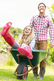 Smiling man pushing his laughing girlfriend in a wheelbarrow — Stock Photo