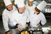 Experienced head chef showing pan to his colleagues — Stock Photo