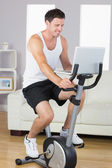 Happy sporty man exercising on bike and using laptop — Stock Photo