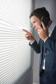 Serious handsome businessman looking through roller blind phoning — Stock Photo