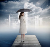 Smiling businesswoman standing on bridge in front of white city — Stock Photo