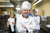 Head chef posing with team behind him — Stock Photo