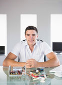 Handsome computer engineer sitting at desk smiling at camera — Stock Photo