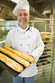 Mature baker presenting proudly some baguettes on a baking tray — Stock Photo