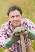 Smiling man posing with a shovel — Stock Photo