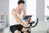 Smiling sporty man exercising on bike and using tablet — Stock Photo