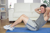 Handsome sporty man doing sit ups looking at camera — Stock Photo