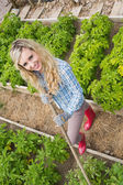 Young woman making use of a rake in her garden — Stock Photo