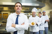 Young restaurant manager posing in front of team of chefs — Foto Stock