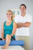 Attractive physiotherapist and patient posing for camera — Stock Photo