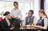 Three business people ordering dinner from waitress — Stock Photo