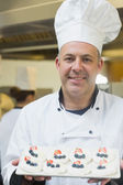 Happy chef presenting plate of meringues — Foto Stock