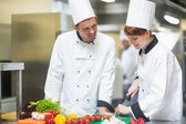 Female chef slicing vegetables with colleague — Stock Photo