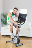 Smiling handsome man training on exercise bike using laptop — Stock Photo