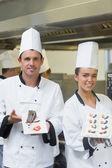 Two happy chefs presenting dessert plates — Photo
