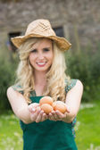 Young blonde woman showing eggs — Foto Stock