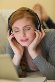 Calm redhead lying on the sofa with her laptop listening to music — Stok fotoğraf