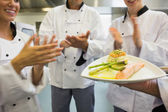 Young chefs applauding a salmon dish — Photo