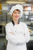Pretty female chef posing in a modern kitchen — Stock Photo