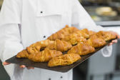 Baker presenting some croissants — Stock Photo