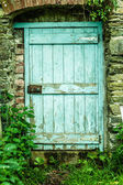 Blue wooden door in a stone wall — Stockfoto