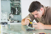 Handsome serious computer engineer repairing hardware with pliers — Foto de Stock