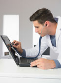 Attractive computer engineer examining laptop with stethoscope — Stock Photo