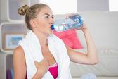 渴了金发女郎,坐在运动垫从瓶水喝 — 图库照片