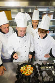 Experienced head chef explaining something to his colleagues — Stock Photo
