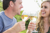 Cheerful couple toasting with white wine — Stock Photo